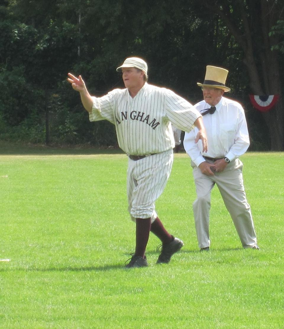 "Pitcher Bob ""Mad Dog"" Madden, one of the Hingham Derby players, makes an underhanded toss to the plate under the watchful gaze of umpire Carl ""Eagle-Eye"" Harris Esq."